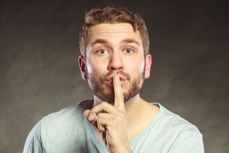 discretion: Young man guy with finger on lips showing hand quiet silence sign gesture in studio on black. Stock Photo