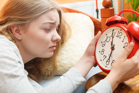 turning off: Unhappy woman waking up in bed turning off alarm clock. Young girl in the morning.