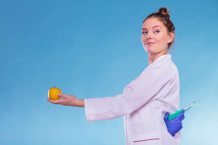 modified: Scientist doctor with apple hiding syringe. Woman chemist holding genetically modified fruit. GM food modification.