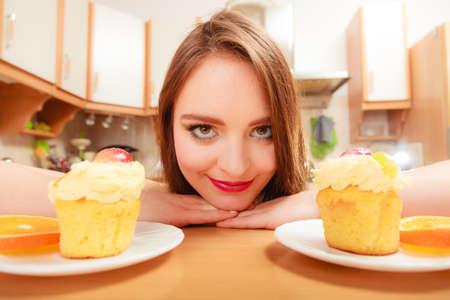 gluttony: Woman looking at delicious cake with sweet cream and fruits on top. Appetite and gluttony concept. Stock Photo