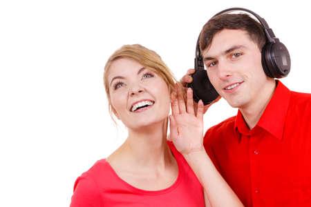 personas escuchando: Par de dos amigos con grandes auriculares escuchando música mp3 juntos. Mujer alegre feliz y el hombre en blanco. La gente de ocio concepto de la felicidad.