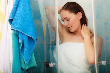 cabine de douche: Girl showering in shower cabin cubicle enclosure. Young woman with white towel taking care of hygiene in bathroom. Banque d'images