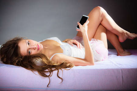 woman dialing phone number: Contact idea. Attractive woman holding smartphone and lying on bed. Gray background.