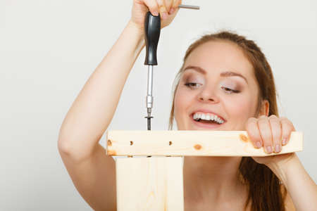enthusiast: DIY enthusiast. Woman assembling wooden furniture using screwdriver. Young girl doing home improvement. Stock Photo