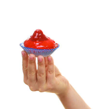 indulging: Sweet food indulging and fattening concept. Delicious tasty sweet cake cupcake in human hand isolated on white Stock Photo