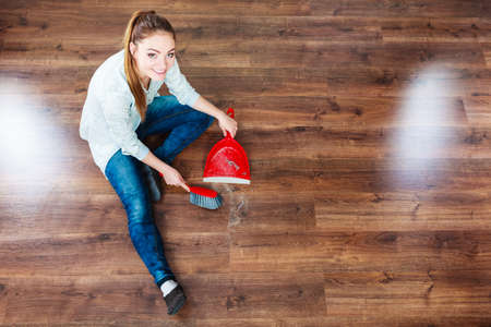 high angle: Cleanup housework concept. cleaning woman sweeping wooden floor with red small whisk broom and dustpan unusual high angle view