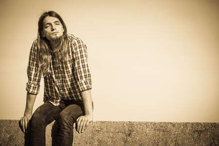 man with long hair: Man long hair wearing plaid shirt relaxing outdoor sitting on concrete wall at sunny day against sky Stock Photo
