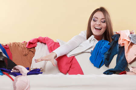 messy clothes: Happy woman picking clothes up off sofa couch in messy living room. Young girl surrounded by many stack of clothing. Disorder and mess at home.
