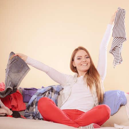 habitacion desordenada: Feliz mujer sentada en el sof� cama en sal�n desordenado sosteniendo ropa. Chica joven rodeada por muchos pila de ropa. El desorden y el caos en el pa�s. Foto de archivo