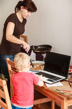 early education: Technology and early education. Spending time with family eat together. Child use laptop for fun and learning. Boy with computer and mother cooking dinner.