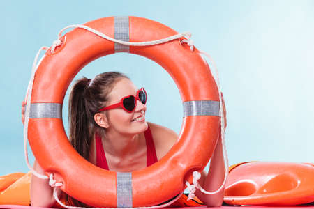glad: Happy glad young woman girl in heart shape sunglasses with ring buoy lifebuoy. Summer safety security.