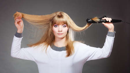 hairstyling: Hairstyling. Attractive blonde woman long haired making hairstyle hairdo with electric hair iron straightener gray background