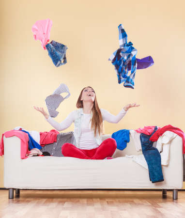 chaos: Happy woman sitting on sofa couch in messy living room throwing clothes. Young girl surrounded by many stack of clothing. Disorder and mess at home.
