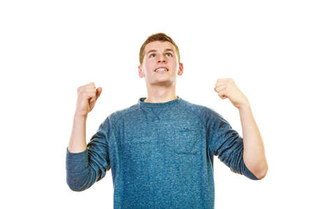 clenching: Success positive emotions. Happy young man successful lad with arms up looking upwards clenching fist isolated on white background