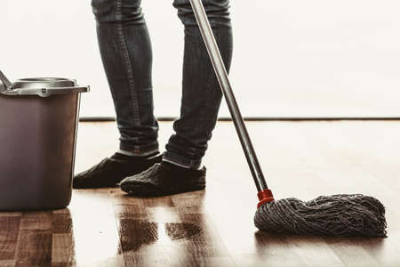 mopping: Closeup of human cleaning mopping floor. Person with mop and bucket at home. House cleanup. Stock Photo