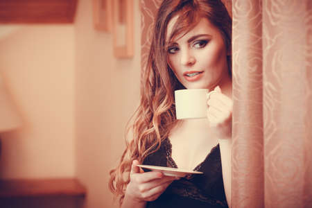 energizing: Sensual seductive woman in lingerie drinking cup of coffee by curtain at home. Young girl with hot energizing beverage stay awake. Caffeine energy. Instagram filter. Stock Photo