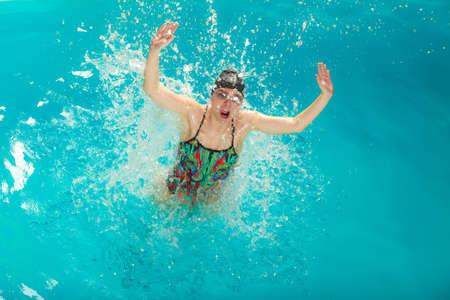 fun activity: Woman in swimming pool water splashing. Girl having fun. Leisure activity. Stock Photo