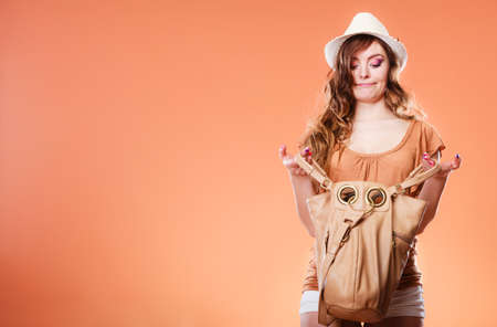 belongings: Summer holidays and vacation. Girl in fashionable clothes straw hat holding bag handbag looking for something. Woman funny face expression on brown