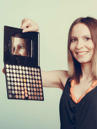 and eyelid: Woman stylist holding professional eyeshadow makeup palette with mirror. Beautyfying eye eyelid. Make up makeover concept. Stock Photo