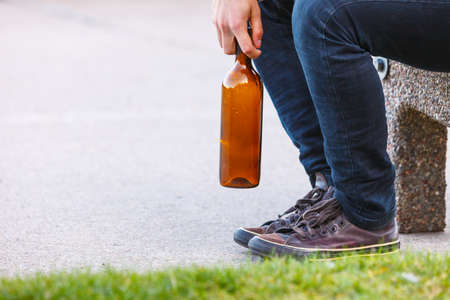 alcoholism: Man depressed with wine bottle sitting on bench outdoor. People abuse and alcoholism problems.