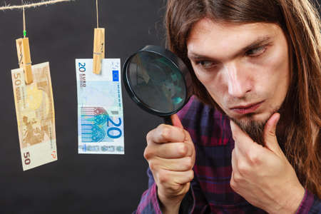 verify: Currency exchange concept. Man worker check verify money cash. Payment hang on laundry line. Guy with loupe.