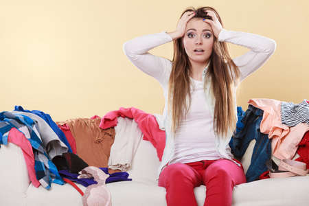 chaos: Desperate helpless woman sitting on sofa couch in messy living room with hands on head. Young girl surrounded by many stack of clothes. Disorder and mess at home.