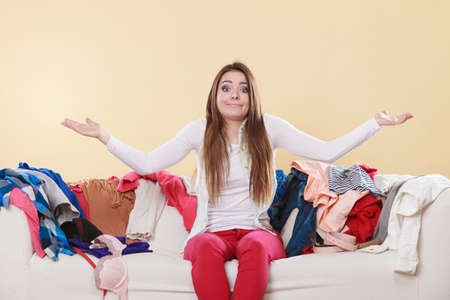 messy clothes: Helpless woman sitting on sofa couch in messy living room shrugging. Young girl surrounded by many stack of clothes. Disorder and mess at home. Stock Photo