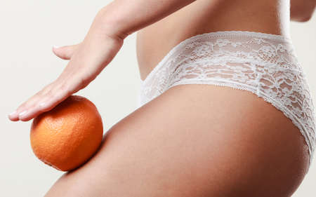 aspects: Absence of cellulite. Part body of slim fit girl holding orange next to the leg  Woman wearing white lacy lingerie. Diet aspects.