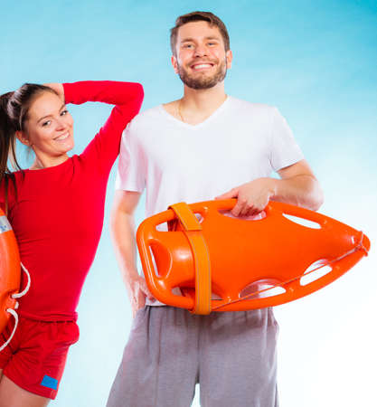 arm holding: Accident prevention and water rescue. lifeguard couple on duty woman leaning on man arm, holding buoy lifesaver equipment on blue Stock Photo