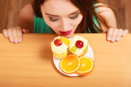 gluttony: Woman hidden behind table sneaking and looking at delicious cake with sweet cream and fruits on top. Appetite and gluttony concept. Stock Photo