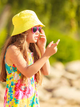 enjoyable: Time for fun. Summer holidays concept. Little funny girl having fun on playground. Child making crazy faces. Enjoyable playful kid outdoors.