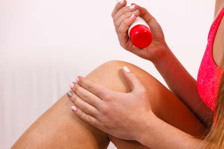waxed legs: Woman fitness girl putting ointment cream on bad injured knee or treating skin with moisturizing cream. Sport training health and skincare
