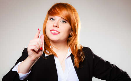disapproving: Young business woman smiling and shaking wagging her finger student girl scolding on gray Stock Photo