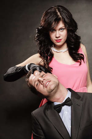 Woman in control of man, sexy female controls her guy. Studio shot on black grey background.