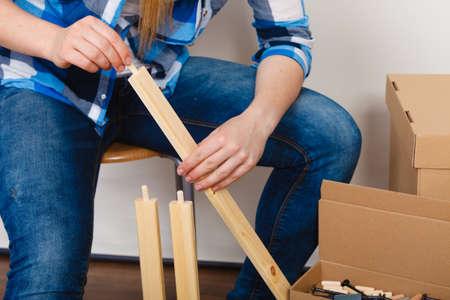 enthusiast: Woman assembling wood furniture. DIY enthusiast. Girl doing home improvement. Stock Photo
