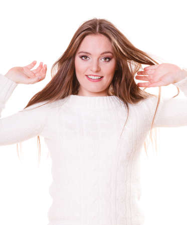 wintertime: Attractive long hair young woman wearing fashionable wintertime clothes white warm sweater studio shot isolated Stock Photo