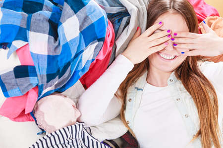 covering eyes: Portrait of happy glad young woman girl lying on stack of clothes covering eyes. Disorder and mess.