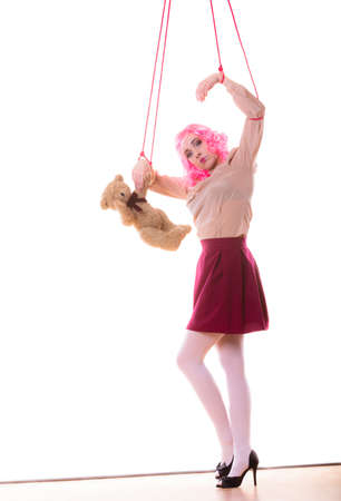 constrained: Mental disorder concept. Young woman girl stylized like marionette puppet on string with teddy bear toy isolated on white background