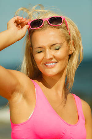 closing time: Young blonde pretty girl on beach closing eyes. Woman wearing sunglasses have active time in summer. Summertime concept.