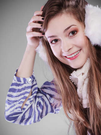 earmuff: Smiling teenage girl wearing fluffy white earmuff in winter fashion, thinking about gift.