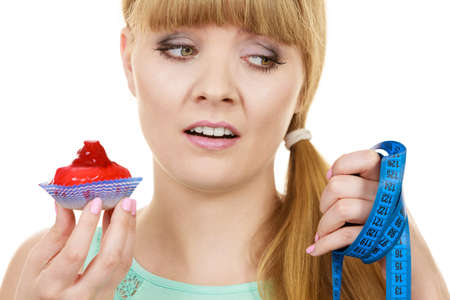 overeat: Woman undecided with blue measuring tape holds in hand cake cupcake, trying to resist temptation. Weight loss diet dilemma gluttony concept. Stock Photo