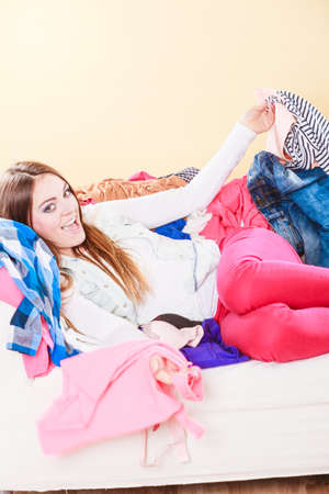 messy: Happy woman in messy room on stack of clothes. Disorder and mess at home. Stock Photo