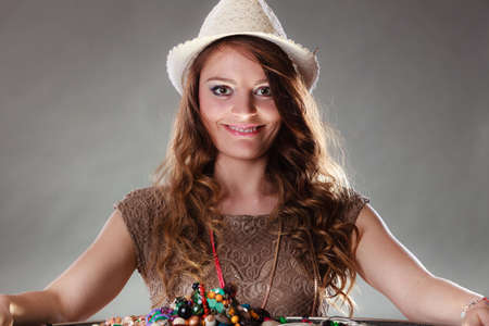 plentiful: Pretty young mysterious woman in hat with many plentiful of precious jewelry necklaces beads. Portrait of gorgeous fashion girl in studio on gray. Stock Photo