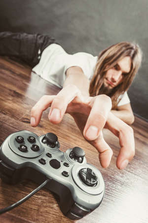 dependency: Addiction and dependency concept. Young man with pad joystick playing games. Male addicted to console