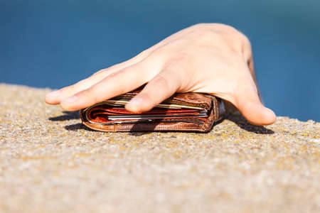unattended: Man thief finding wallet on sea shore taking stealing it. Leaving belongings unattended and risk of theft