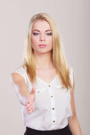 pacto: Mujer de negocios joven que hace invitating de bienvenida de los pulgares o la palma para dar apretón de manos. Tiro del estudio sobre fondo gris