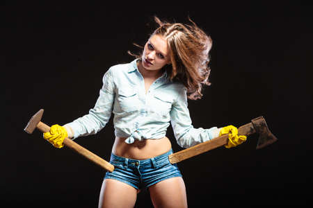 axes: Sexy seductive woman holding axes choppers. Strong girl feminist working in man profession. Independent female.