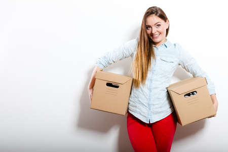 arranging: Happy woman moving in carrying cartons boxes. Young girl arranging interior and unpacking at new apartment house home. Stock Photo