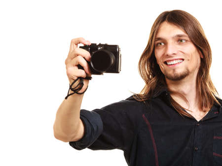 goodlooking: Man taking photo picture with camera. Handsome young guy male with long hair isolated on white background. Stock Photo