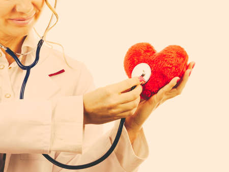 proffesional occupation: Medical examination of cardiology. Cardiologist with heart and stethoscope. Female doctor in white uniform makes measurement heartbeat. Filtered.